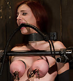 Redhead with big tits, bound in extreme metal bondage