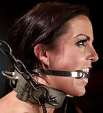 Brunette bound with stocks, straps and chains