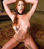 Redhead tied, clamped and trained by couple