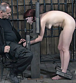 Naked redhead cuffed, put in stocks and caned