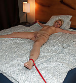 Blond in cut open pantyhose tied fully spread